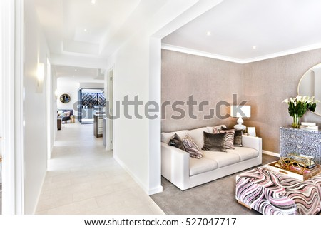 Modern House Interior With A Hallway And Living Room Including Pillows On Sofas Beside Mirror
