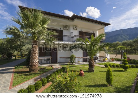 Modern house with a beautiful garden with lawn and palms - stock photo