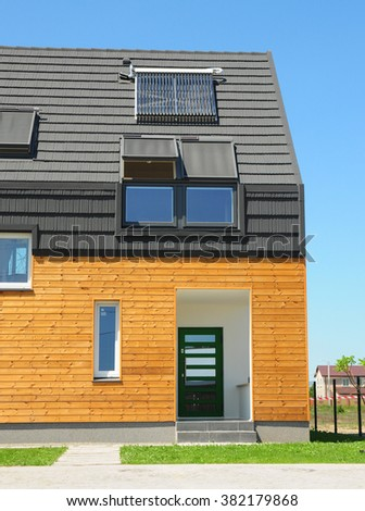 Modern House with Energy Efficiency Solution Concept Outdoor.  New Building House Solar Energy, Solar Water Heater, Solar Panels, Skylights,  Installed on Roof Asphalt Shingles - stock photo