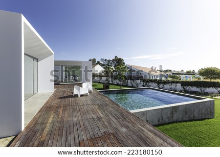 Modern house with garden swimming pool and wooden deck - stock photo