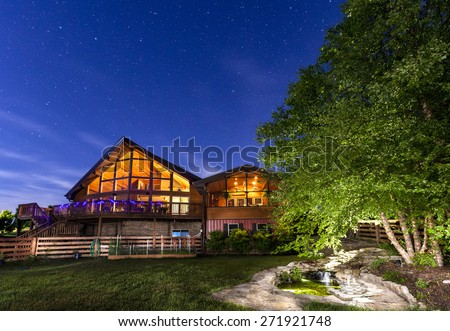 Modern house with koi pond under starry skies - stock photo