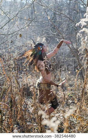 Modern Indian-style girl in a horned and feathered hat, dancing tribal and shamanic ritual dances.