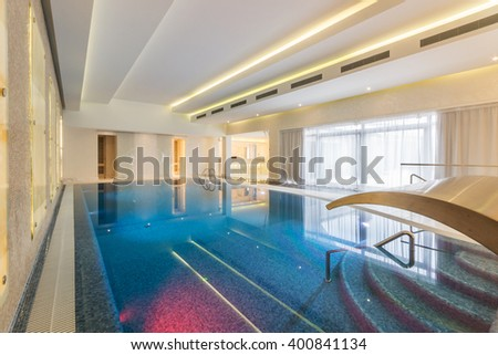 Modern indoor pool with waterfall jet in SPA at hotel