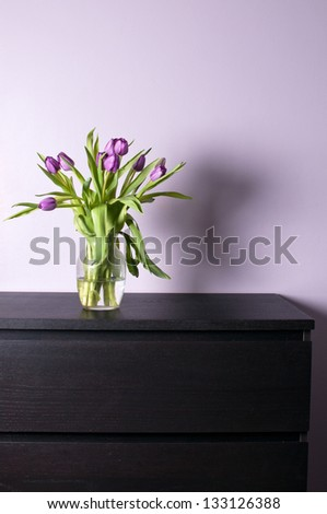 Modern interior chest drawer decorated with flowers - stock photo
