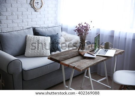 Modern interior. Comfortable workplace. Wooden table with beautiful bouquet of flowers and laptop on it.
