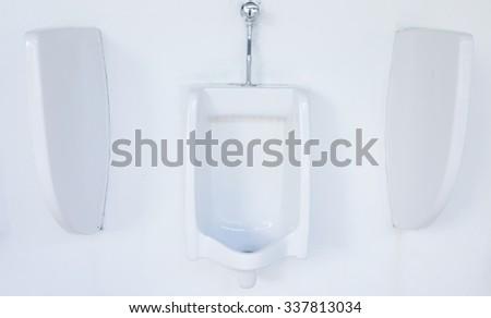 Modern interior design of white ceramic urinals for men - stock photo