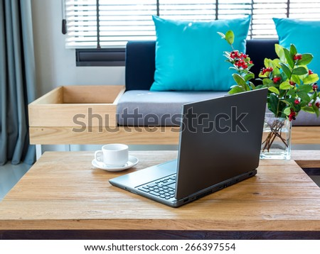 Modern interior Living room with laptop on table top/ sofa background - stock photo