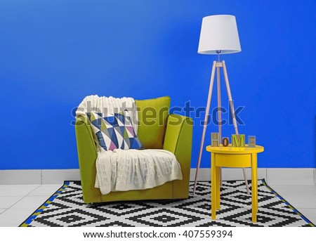 Modern interior of room with armchair on blue wall background - stock photo