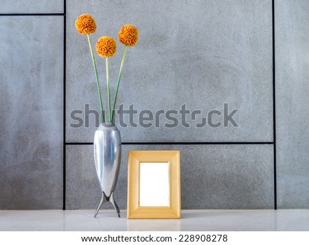 Modern interior wall with vase of flowers and blank picture frame - stock photo