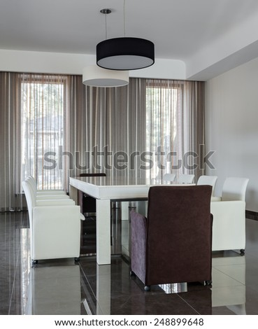 Modern interior with big table and chairs in daylight - stock photo