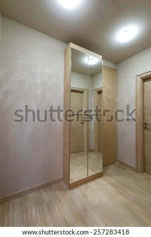 modern interior with bright wooden wardrobe with mirror - stock photo