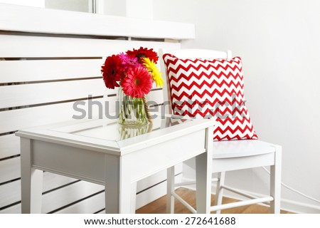 Modern interior with white chair and pillow near coffee table with colorful gerbera - stock photo