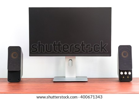 Modern ips computer monitor with speaker on wooden table. Home use for work or entertainment. White cement wall background.