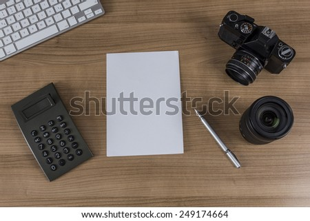 Modern keyboard a calculator a blank sheet and a vintage camera and a pen on a wooden desktop - stock photo