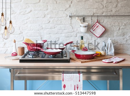 modern kitchen behind brick wall with red cookware set, modern lamp