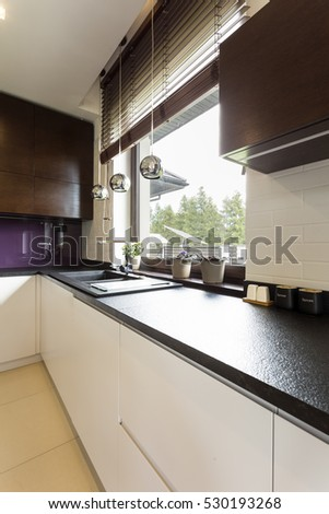 Modern kitchen corner with dark worktop, violet splashback and white cabinets
