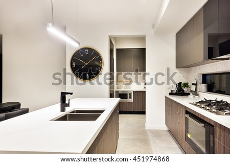 Modern kitchen counter top closeup with a stove and watch beside the oven and pantry cupboards, the counter included a tap and sink under the  hanging tube light - stock photo
