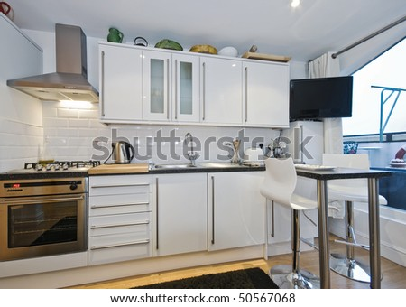 modern kitchen counter with breakfast bar and tall chairs - stock photo