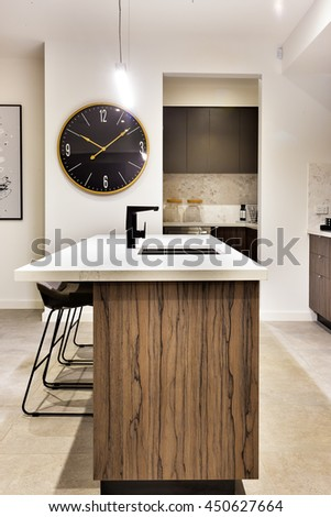 Modern kitchen countertop made in wood with a wall watch and chairs of a luxury house - stock photo