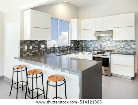 Modern Kitchen In White With Bar Stools And Grey Counter Top.