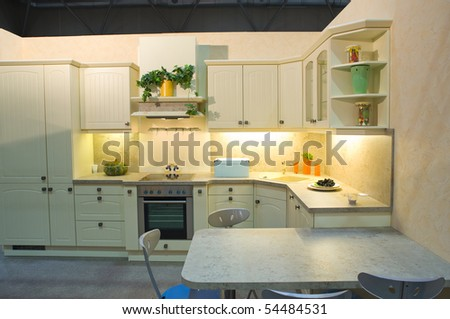 Modern kitchen in white with decoration, stools and table