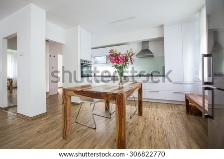 Modern Kitchen Interior Design Architecture Stock Image, Photo of a modern white kitchen with a dark wood table, hi-end appliances and plenty of daylight - stock photo