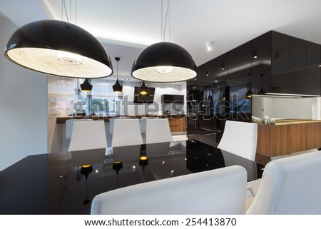 Modern kitchen interior design in black and white style with black table - stock photo