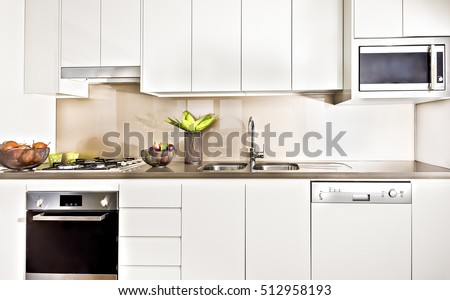 Modern kitchen interior  illuminated with lights, oven and gas cooker have attached to the pantry cupboard, flower pot near the wash basin, pantry cupboard is white color, ceramics and fruits