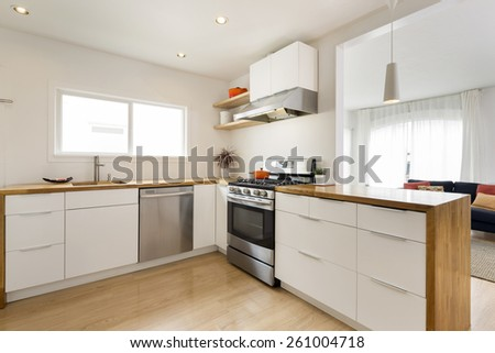Modern kitchen interior in loft with white cabinets and amazing wooden counter top. Amazing Design concept. - stock photo