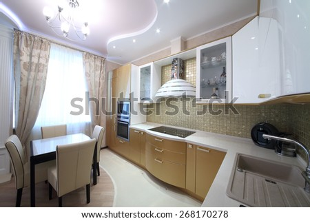 Modern kitchen interior with golden cabinets in the apartment - stock photo