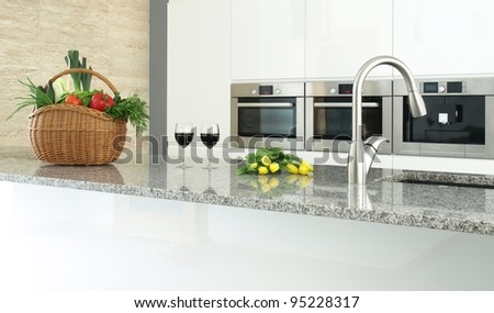 Modern kitchen interior with vegetables, glasses of wine and flowers - stock photo