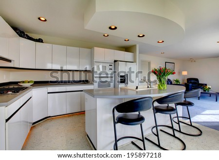 Modern kitchen interior with white storage combination and appliances. Room decorated with fresh tulips. - stock photo