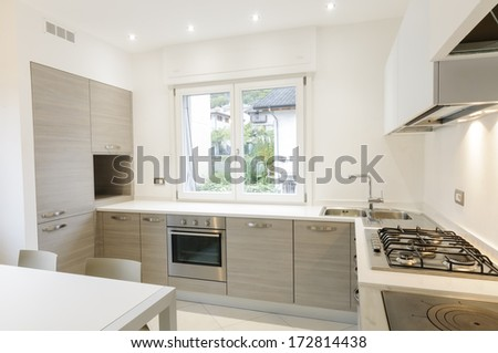 Modern kitchen interior with wooden cabinets and white table - stock photo