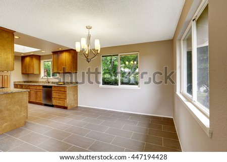 Modern kitchen room with matte brown cabinets, shiny granite tops, steel stove with hood and tile floor