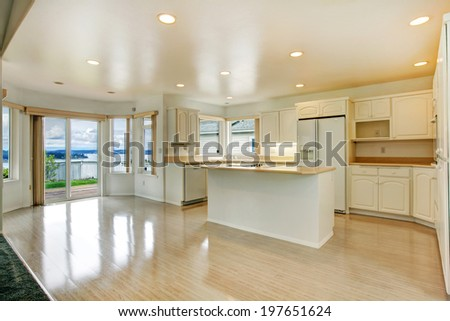 Modern kitchen room with shiny hardwood floor, white cabinets and appliances. View of kitchen island
