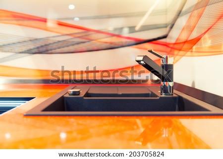 Modern kitchen sink in orange ceramic - stock photo