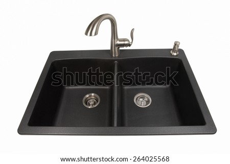 Modern kitchen sink made of black synthetic granite with brushed stainless steel faucet and soap dispenser.  Isolated on a white background.  Viewed from front.  Contemporary living and design. - stock photo