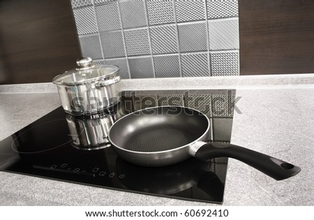 Modern kitchen. Steel pot and pan on the induction cooker - stock photo