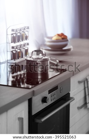 Modern Kitchen Table With Electric Stove, Utensils And Spices Beside The  Window
