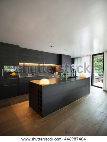 Modern kitchen with black furniture and wooden floor - stock photo