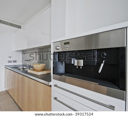 modern kitchen with built in coffee machine in stainless steel