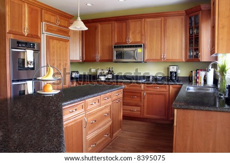 Modern Kitchen with Cherry Cabinets and Granite Countertops - stock photo