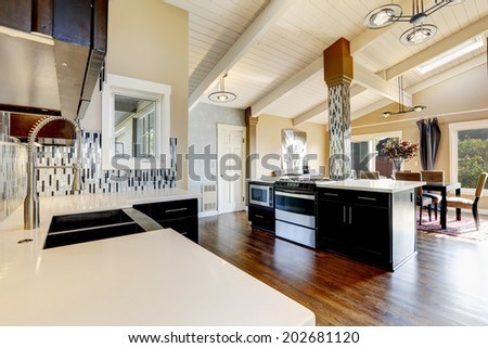 Modern kitchen with dark brown cabinets, steel appliances and kitchen island with bar stools