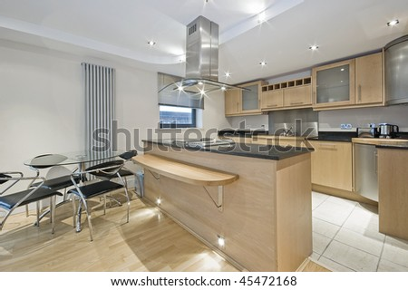 modern kitchen with dining area and breakfast bar - stock photo