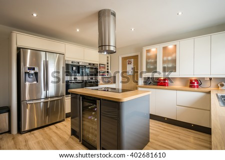 Modern Kitchen with Island / A modern domestic kitchen with high gloss units, rounded corners and an island - stock photo