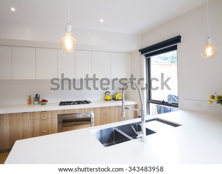 Modern kitchen with pendant lighting and sunken sink in island bench - stock photo