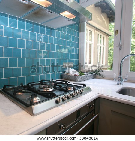 Modern kitchen with turquoise tiles on wall looking onto garden - stock photo