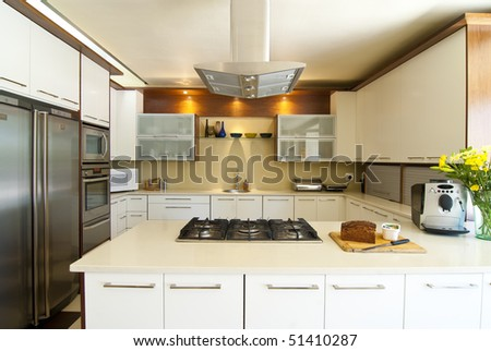 Modern kitchen with white and wood finished, and a silver hob overhead - stock photo