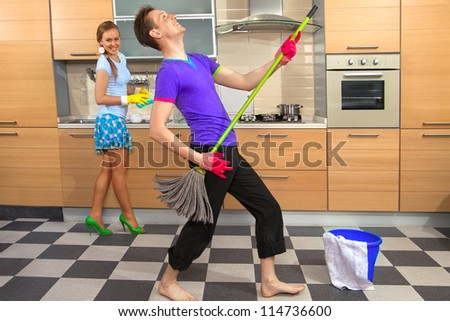 Modern kitchen - woman with sponge and smiling young man cleaning the floor at home and pretend to sing song with mop - stock photo
