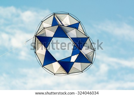 modern kite with abstract shape and white and blue colors flying in blue sky - stock photo
